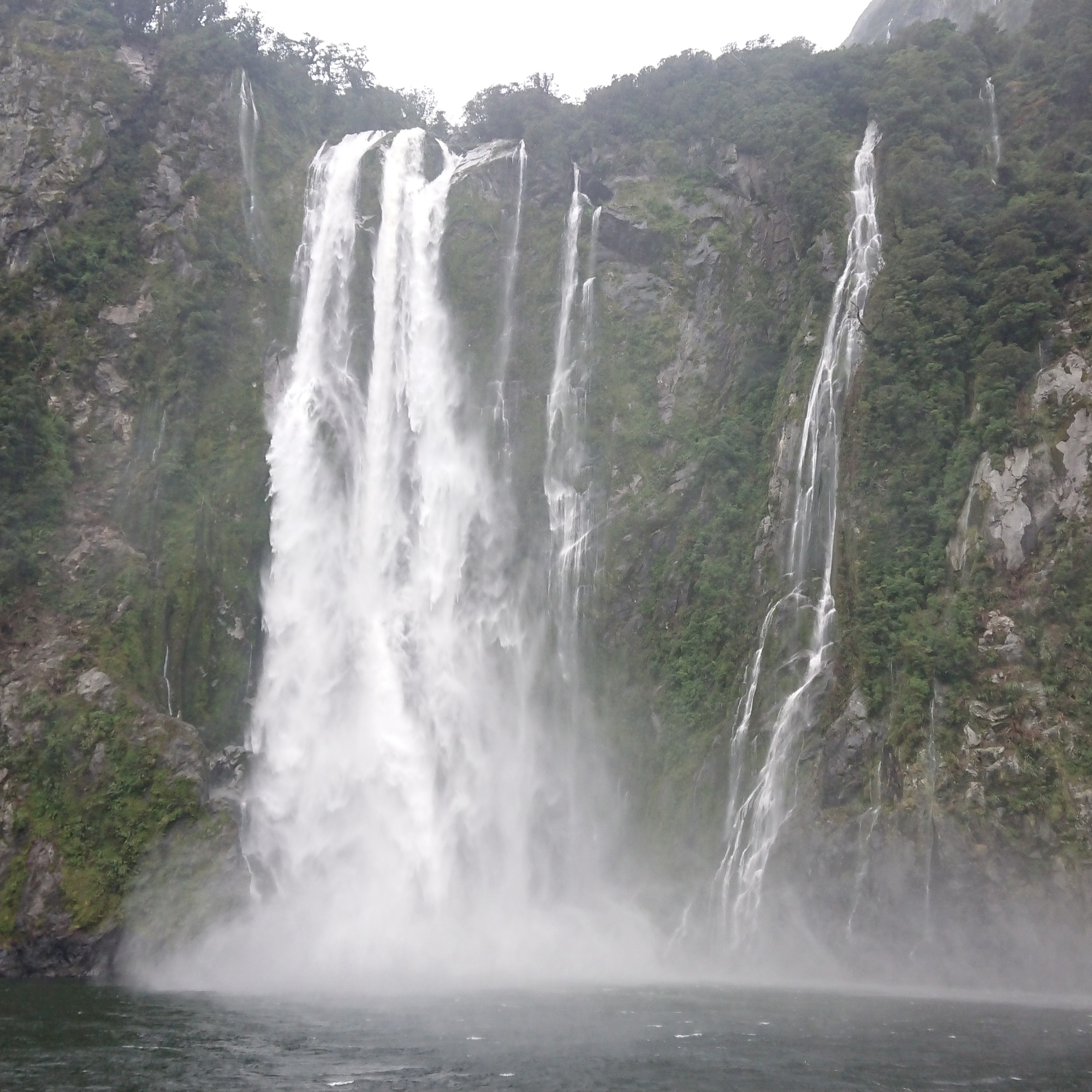 A large waterfall in Milford Sound crashing from the rocks above