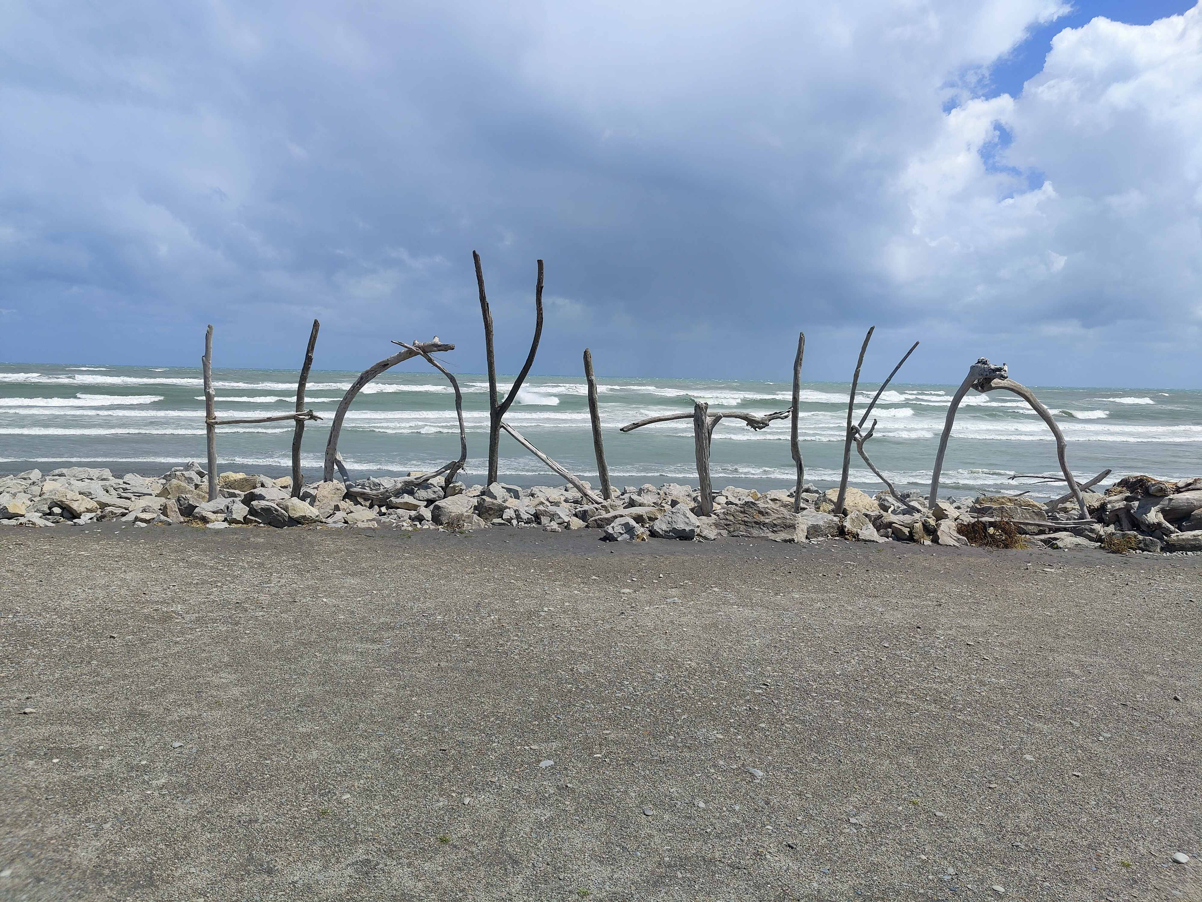 A sign of Hokitika made of sticks on the beach