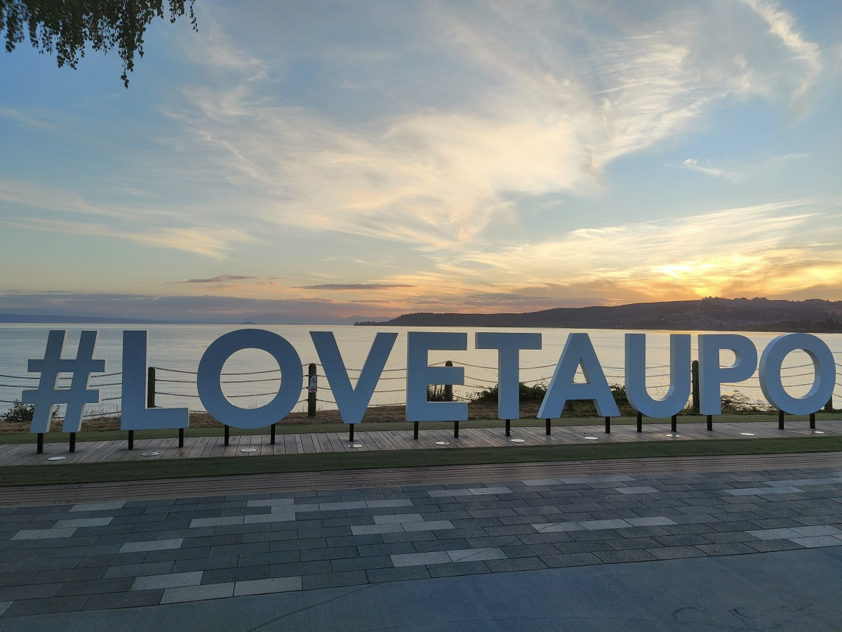 #LoveTaupo sign in front of Lake Taupo at sunset