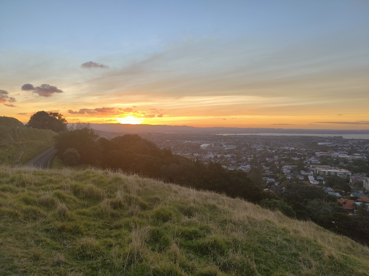 The sun drops below the horizon while on Mt Eden